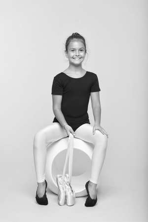 Child flexible gymnast practice stretching tiptoes. Child tender dancer look gorgeous fancy leotard. Dream every girl become famous gymnast. Kid sit hold pointe ballet shoes. Special shoes for ballet 写真素材