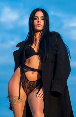 Sexy beautiful girl in lace underclothes. sensual seductive attractive brunette in coat. she is wearing hot sexy lingerie with panties. ladies fashion concept