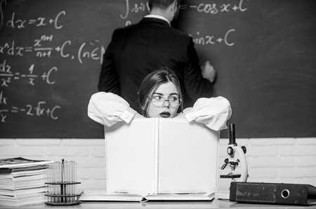 Thinking hard. Pretty teacher giving homework. Student writing homework on chalkboard. Doing homework together. Homework assignment and task. School and education. Teaching and learning