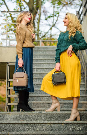 Good mood at any weather. girl friends go upstairs. fall season color trends. Pleated trend. girls in corrugated skirt and sweater. female beauty. knitwear fashion. stylish autumn women outdoor
