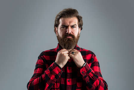 Bearded man fastens his shirt.. Hair and beard care. Confident and handsome brutal man.