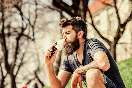 man smoking e-cigarette. Mature hipster with beard. Bearded brutal male smoking electronic cigarette.