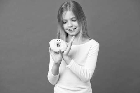 Girl on smiling face holds sweet donut in hand, violet background. Sweet tooth concept. Girl looking at donut with pair of eyes. Kid girl with long hair likes sweets and treats 版權商用圖片