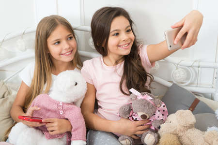 Virtual world. Little girls use phone in bed. Taking Christmas and New Year selfie with smartphone. Happy little children with mobile phone. Merry Christmas and Happy New Year greetings