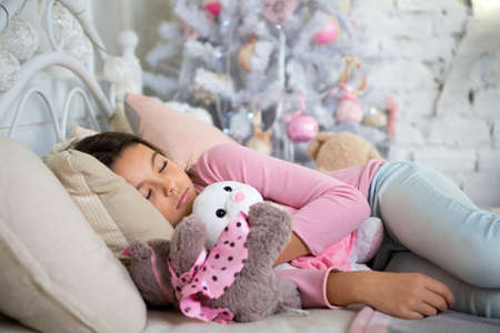 delivery christmas gift. little child girl with xmas present. happy new year. happy little girl celebrate winter holiday. christmas time. morning before Xmas. sleeping and dreaming. Christmas is here