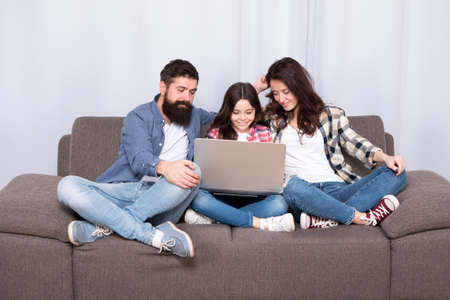 happy family using laptop. Stay online. little girl with parents. mother and bearded father with daughter looking at laptop. digital device in modern life. cyber monday. family blog on laptop