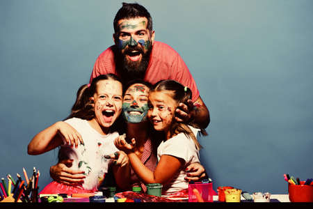Parents and children painted with gouache on blue background. Girls, man and woman with cheerful faces by art desk Imagens