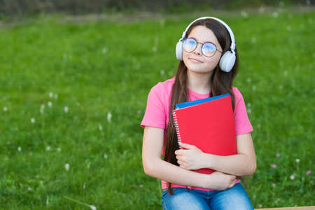 Girl listening summer melody wireless headphones nature background, hobby and leisure concept Banque d'images
