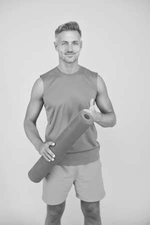 Workouts with modifications for different levels. Yoga is my hobby. Personal training. Meditations designed to help you find your joy. Man practicing yoga at home. Handsome sportsman with yoga mat