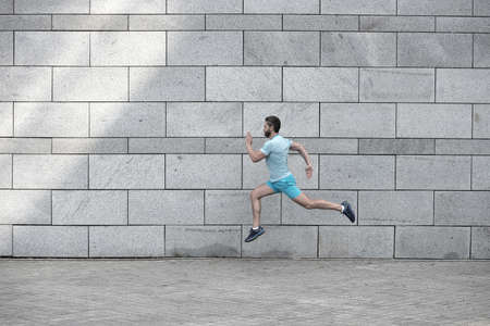 man running outdoor. Healthy male runner. hurry up. Full length portrait of fitness guy running. Achievement of success and excellence. Athlete running against concrete wall. Sport man starts to run