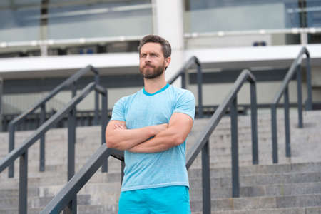 Handsome athlete beard man standing confidently. Staying fit and healthy. having a good sport shape. he is always in great shape. serious bearded man crossed hands. feeling confident and successful
