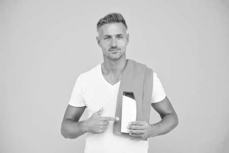 Body care. Presenting product. Cosmetics for men. Male shampoo. Beauty product. Mature man fit body. Sport and fitness. Perfect for daily use. Handsome well groomed healthy guy recommend product 写真素材