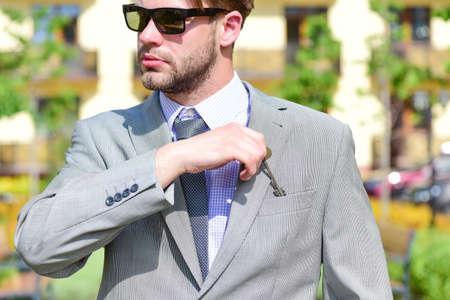 Estate agent puts key into pocket. Man in yard