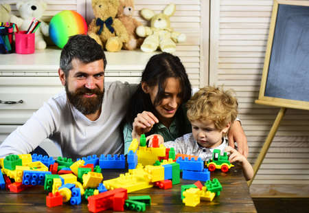 Mom, dad and boy build out of plastic blocks