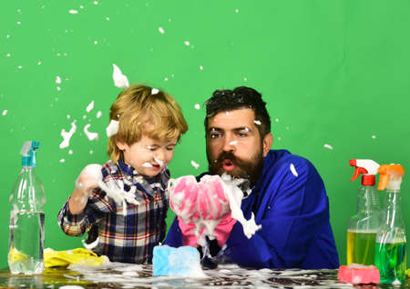 Dad with son and cleaning supplies on green background.