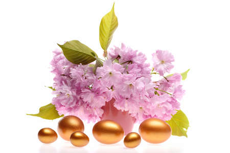 Easter eggs of golden color in different size with sakura