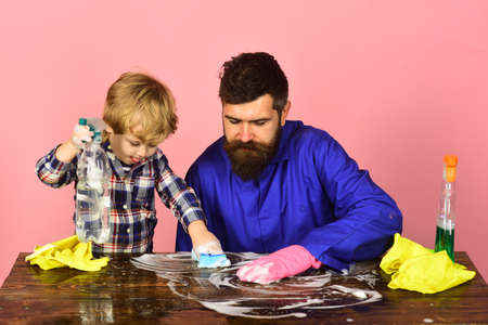 Son with father cleaning together with sponges