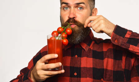 Farmer with calm face uses cherry tomatoes as straw