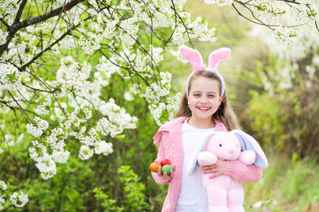 Happy girl holding pink rabbit toy and eggs