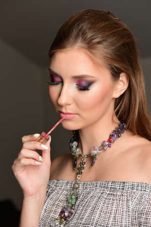 Model painting lips with lip gloss with seductive face expression