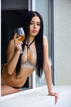 Attractive sexy brunette female in lingerie drink wine in glass. portrait with glass and champagne. Woman relaxing at home. Luxury life. Woman in erotic underwear. bra and panties. Rich sexy chic
