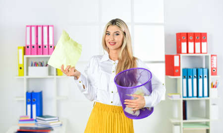 Businesswoman hold trash can. Girl looking for lost document. Lost due to distraction. Cancel file deletion. Dispose of waste paper. Paper recycling. Crumpled paper in basket. Woman hold garbage bin Stok Fotoğraf
