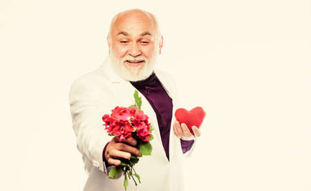 This is for you. Gentleman concept. True gentleman. Handsome bearded man wear tuxedo. Romance and dating. Dating services for elderly people. Senior gentleman romantic. Man hold heart symbol of love Foto de archivo