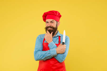 satisfied bearded chef. brutal butcher in apron. best menu offer. confident bearded happy chef red uniform. Male chef cut with knife. mature hipster with happy face