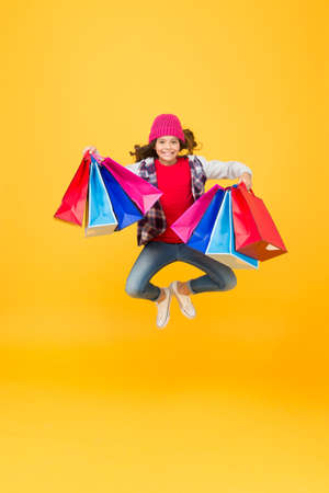 Keeping your purchases safely. Happy girl jump with shopping bags. Energetic shopper carry bags yellow background. Pack and package. Shopaholics best begs forever. Wholesale prices. Shop today