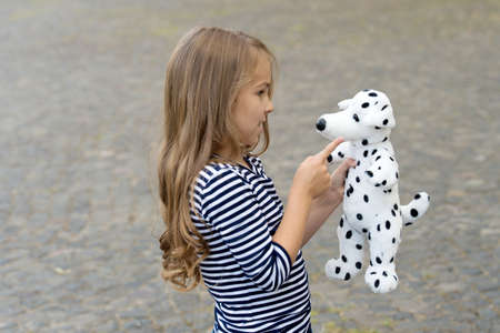 Paying is state of being. Little child play with toy dog outdoors. Role playing. Pretend play. Child development. Developing communication skills. Childhood fun. Playing and learning