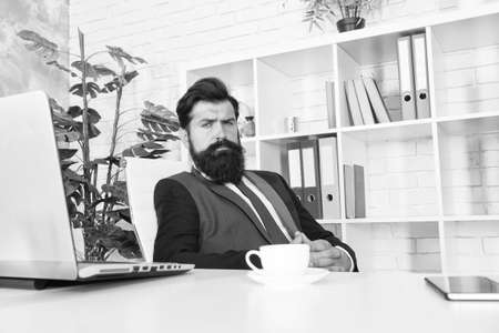 Office life is unthinkable without good coffee. Reception room. Respectable ceo. Man handsome boss sit in office drinking coffee. Comfy workspace. Bearded hipster formal suit relaxing with coffee Фото со стока