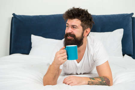 Man happy bearded face drink morning coffee relax in bedroom, perfect awakening concept