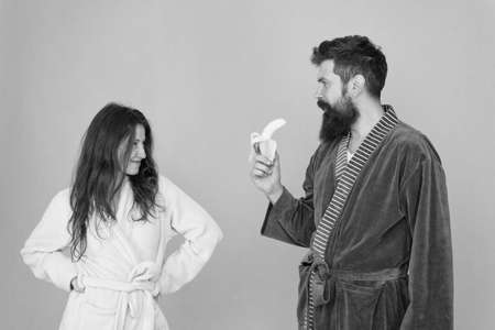 Erotic games for couple. Couple in love blue background. Sensual couple. Sexy woman look at bearded man eating banana. Blowjob and desire. Mens health and potency. Family couple in home clothing Фото со стока