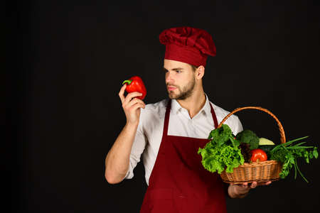 Chef in burgundy uniform holds red pepper in hand. Stock Photo