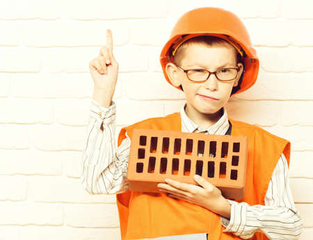 young cute builder boy on white brick wall background