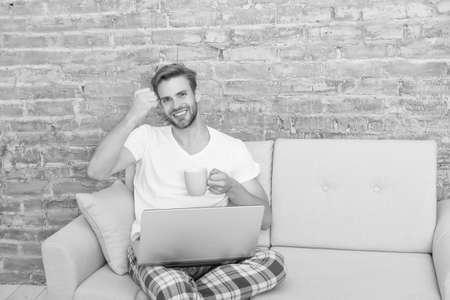 happy male on sofa. guy enjoying internet. social media addiction. computer addict. flirt and send text message. 스톡 콘텐츠