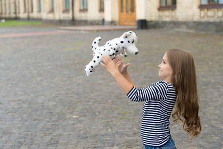 Happy kid play with toy dog outdoors. Enjoying playtime. Play and fun.