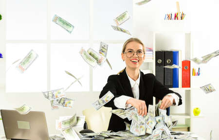 she earn dollars. modern life and business. corporate leather bag. sexy woman with case at workstation. happiness and success. Businesswoman holding briefcase. suitcase with money. good deal