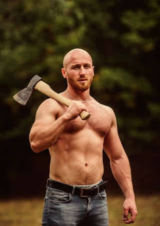 Handsome shirtless man muscular body. Bodybuilding sport concept. Muscular body. Forester with axe. Last man on planet. Sexy macho bare torso. Surviving in wild nature. Muscular athlete in forest