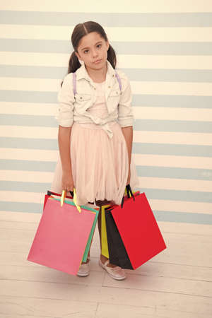 Shopping tiring exhausting activity. Child carries shopping bags striped background. Kid girl spend day buy things supplies for school. Back to school sales season. Girl exhausted holds bags