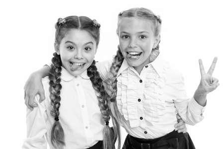 Schoolgirls wear formal school uniform. Sisters little girls with braids ready for school. School fashion concept. Be bright. School friendship. Sisterhood relationship and soulmates
