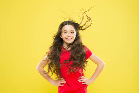 Girl adorable kid long wavy hair yellow background. Strong persistent winds can create tangles and snags in wavy and curly long hair. Things you doing to damage your hair. Wind can also damage hair