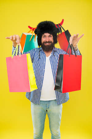 Keep smiling and carry on bags. Bearded man smiling with paper bags after seasonal sale. Happy hipster in bull horns hat holding shopping bags. Carrying purchases in colorful non grocery carrier bags