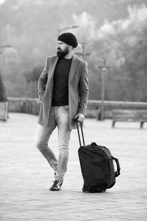 Ready to travel. Carry travel bag. Business trip. Man bearded hipster travel with big luggage bag on wheels. Let travel begin. Traveler with suitcase waiting transportation to airport railway station
