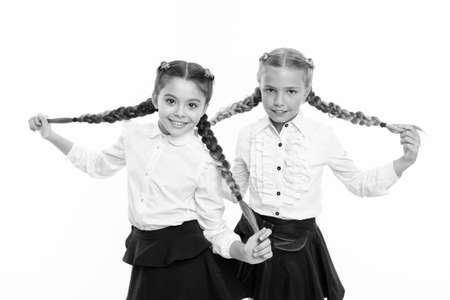 Schoolgirls wear formal school uniform. Sisters little girls with braids ready for school. School fashion concept. Be bright. School friendship. Sisterhood relationship and soulmates. On same wave