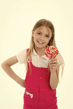 Little girl with lollipop. Little girl hold lollipop candy on stick. Happy childhood years. She has a sweet tooth. Food that reminds you of your childhood