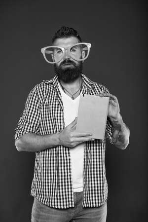 Hipster bearded man wear funny eyeglasses hold notepad or book. Bright up your day. Read this book. Comic and humor sense. Funny story. Study is fun. Funny book for relax. Book cover copy space Stock fotó