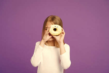 Sweet mood. Child look in donut on violet background. Little girl with glazed ring doughnut on purple background. Kid with junk food. Food and dessert. Childhood and childcare, copy space