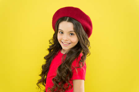 Smiling child. Kid girl long healthy shiny hair wear red hat. Little girl with long hair. Kid happy cute face adorable curly hair yellow background. Lucky and beautiful. Beauty tips for tidy hair