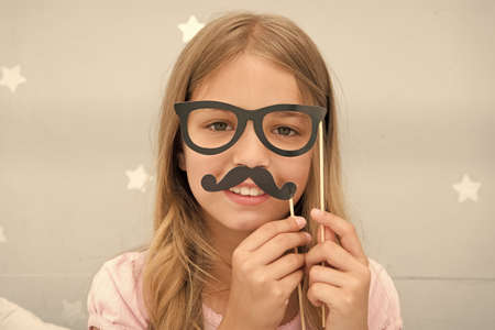 Girl pose with photo booth props glasses and mustache in bedroom. Child girl with party glasses. Child imitate masculinity or want look like her dad. Kid with mustache and eyeglasses